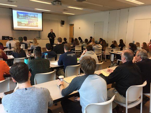 Full classroom of students listen to speaker.