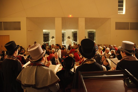 Students don Dickensian garb for pre-concert caroling at the Wassail banquet.