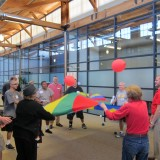 Stroke survivors at Chapman University's Stroke Boot Camp launch balloons off a colorful parachute as part of their physical therapy.