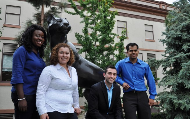 people smiling in front of panther statue