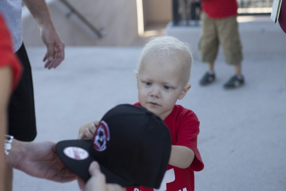 Three-year-old Ben Teach, son of Liz Teach ('04),  is presented with a baseball cap from Chapman Athletics cap during a recent tour of the football facilities. Ben is awaiting a bone marrow transplant and the football team is hosting a campus bone marrow registry drive in hopes of helping find him a donor match.