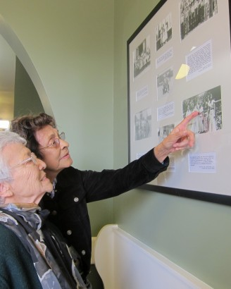 Catalina Figueroa, left, and Emma Cornejo Felix locate family members and friends among the historic photo displays installed in the old Cypress Street School. The women were among several former students who attended ribbon-cutting ceremonies for the new research facility now housed there.
