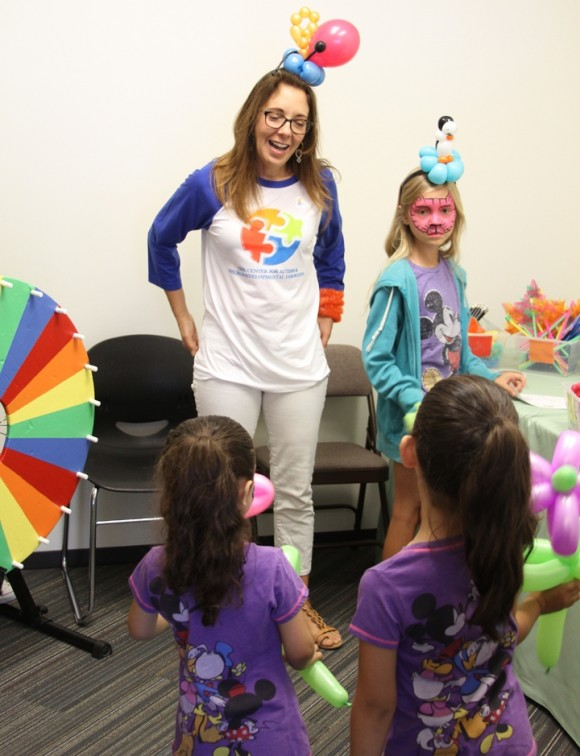 Jeanne Anne Carriere, director of Chapman's C.A.P. Program for the Center for Autism, greets kids in the face-painting room during the Center's grand opening May 10.