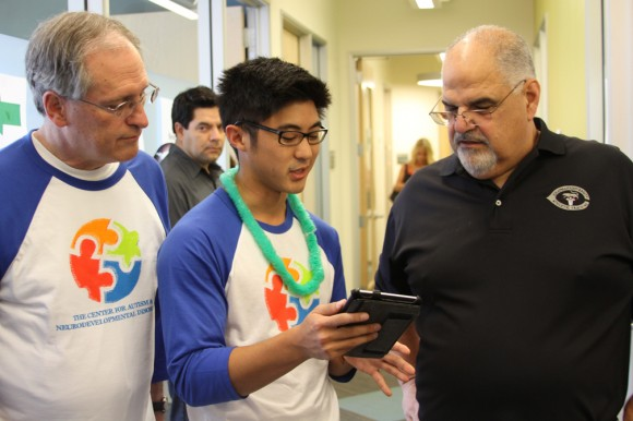 Jared Izumi, CES school psychology student, shows an app he created to Joe Donnelly, M.D. (at left), director of the Center for Autism, and Don Cardinal, Ph.D., incoming director. The app will help families keep connected with autism programs in their local schools.
