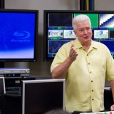 man talking in front of tvs