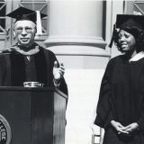 man speaking at podium and woman smiling at commencement