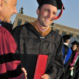 graduate shaking hands and holding diploma