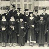 graduating class standing with diplomas