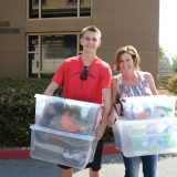 Young man and mother carry boxes