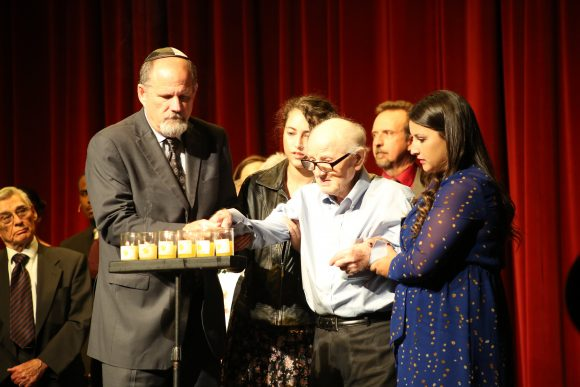 group of people lighting a row of 6 candles