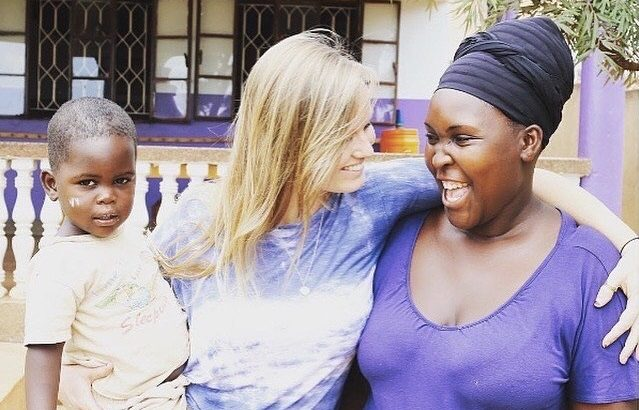 Two smiling women and a small child share an embrace.