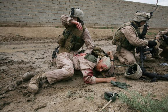 Sgt. Jesse E. Leach tends to Lance Corporal Juan Valdez after Valdez was shot by a sniper on Oct. 31, 2006, in Karma, Iraq. (Photo by Joao Silva/The New York Times/Redux)