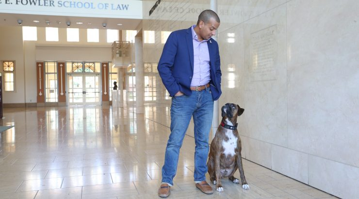 Law student Juan Valdez, a veteran, with service dog Tank