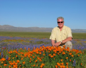 Huell Howser in a field of orange poppies