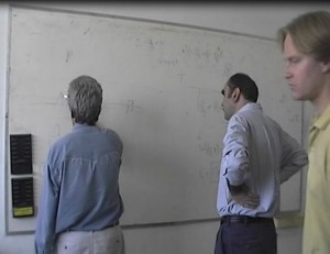 Professors working and writing on a white board