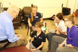 young people adresing an older man's knee for therapy