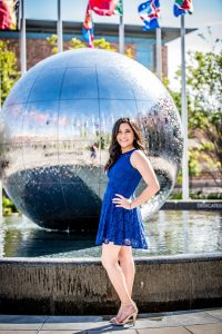 young woman standing in front of a large water ball