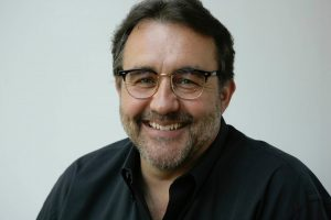 man's face smiling with short beard and glasses