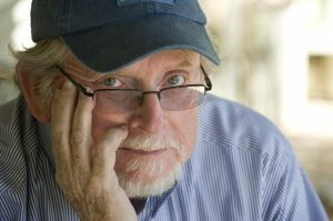 man wearing a baseball cap and glasses holding his face looking at camera