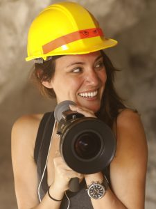 young woman wearing a hard hat and holding a megaphone, smiling