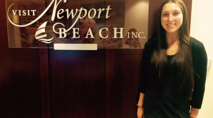Student next to Newport Beach Inc. sign