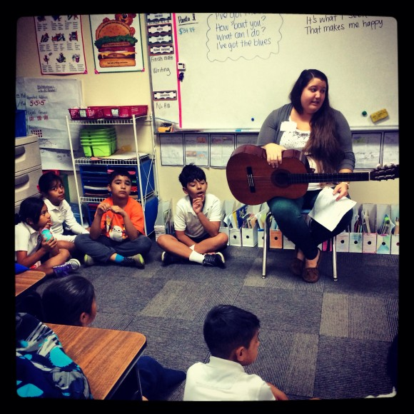teacher with guitar sitting with young students