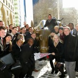 Argyros students and Dean by bull statue on Wall Street