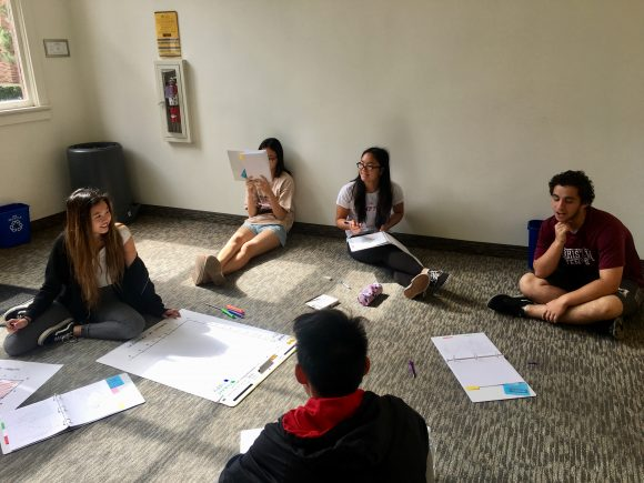 Students sitting on floor working on a group assignment