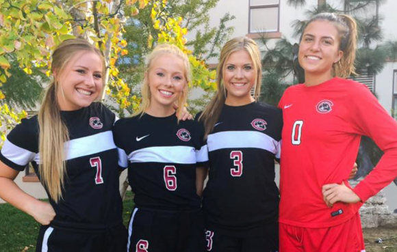 Four women soccer players posing and smiling for a photo in their Chapman team uniforms.