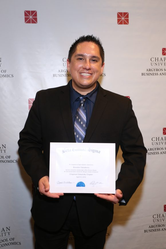 Brandon Salvatierra smiling holding his Beta Gamma Sigma Certificate