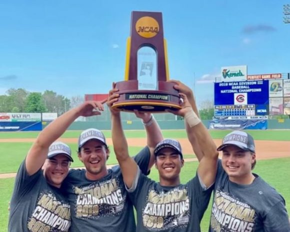 Four Chapman baseball players hold up national championship trophy