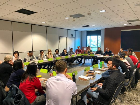 Participants seated in a circle participating in a Colloquium Discussion