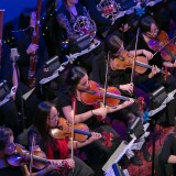 Orchestra playing music, focus on strings.