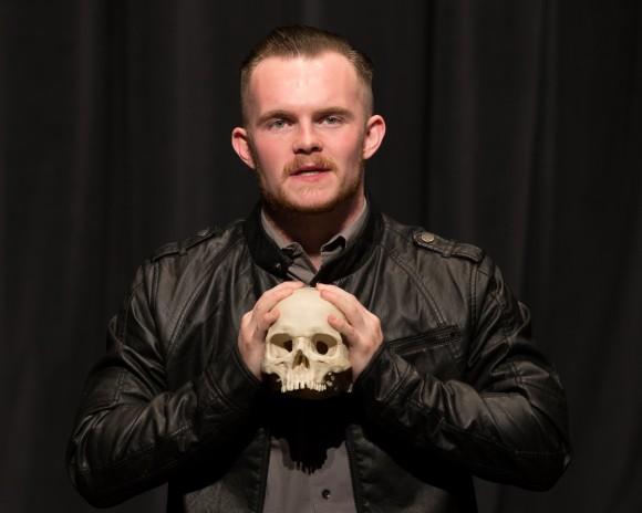 Man holding a skull, acting.