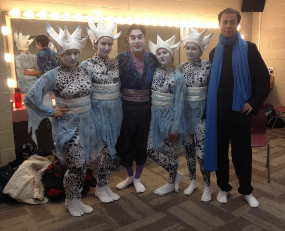 Students pose backstage in costumes at festival.