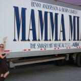 Woman standing next to truck with Mamma Mia! logo.
