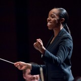 Conductor smiling and holding her baton.