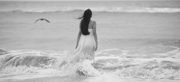 Woman in long white dress walking into the ocean.