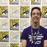 young man with short dark hair standing and smiling in front of a ComicCon backdrop