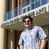 Young man with short dark hair, mustache and sunglasses standing in front of Musco Center.