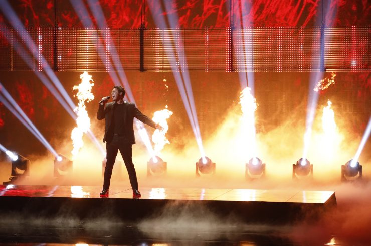 Young man singing on stage with flames in the background