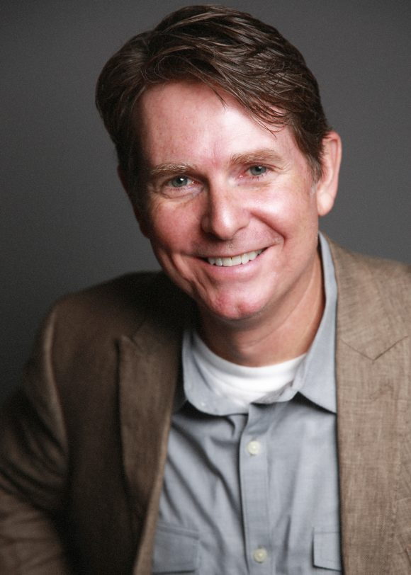 Smiling middle-age man with short brown hair in sport coat and unbuttoned collard shirt