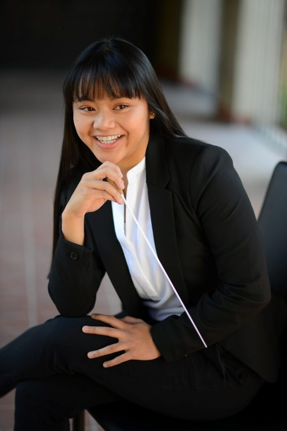 smiling Asian female in black suit seated and leaning forward with music baton in hand