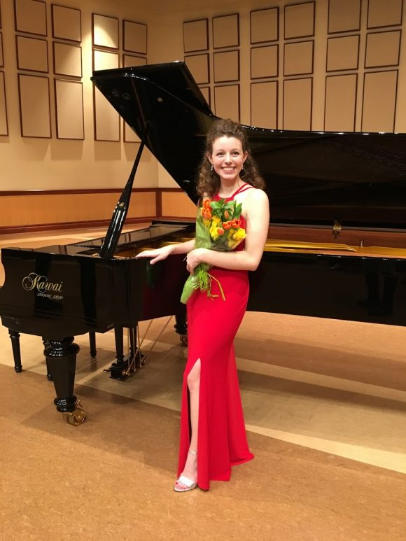 young smiling Caucasian woman in floor length sleeveless gown holding flower bouquet next to grand piano