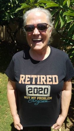 smiling woman in sunglasses and dark t-shirt that reads retired 2020 not my problem anymore