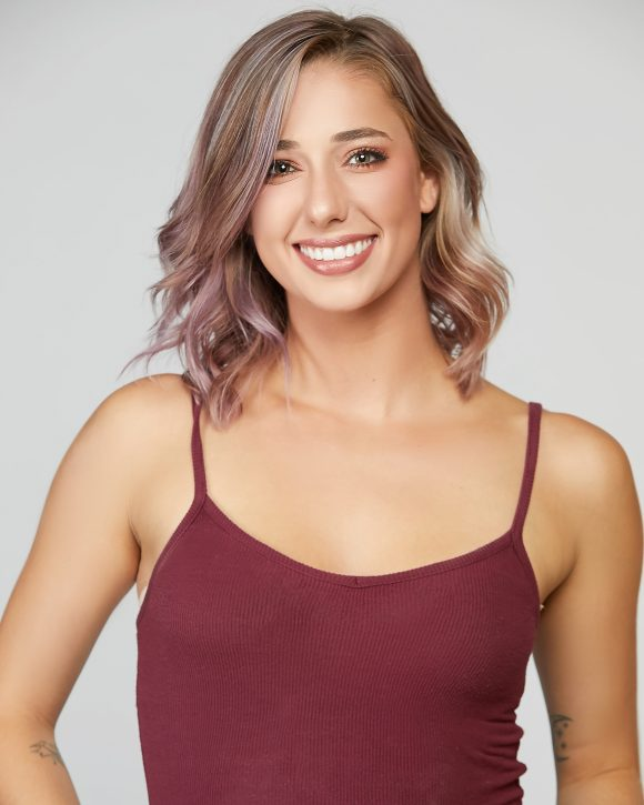 young smiling Caucasian woman in burgundy camisole top