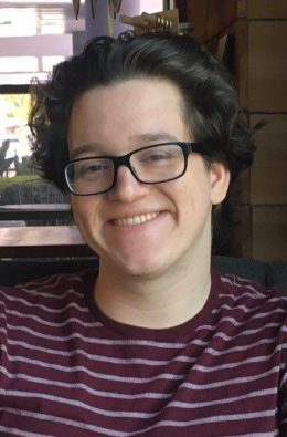 smiling young Caucasian male with short dark hair and black-rimmed glasses in burgundy striped shirt