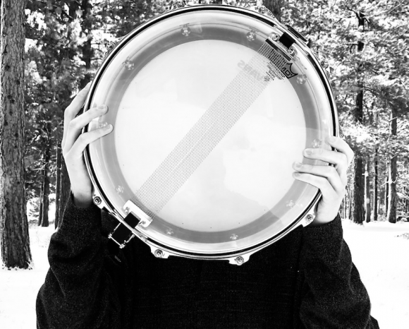 person holding snare drum in front of their face with snow and trees in background