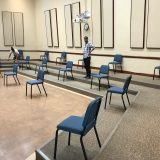 Large room with people moving chairs far apart.