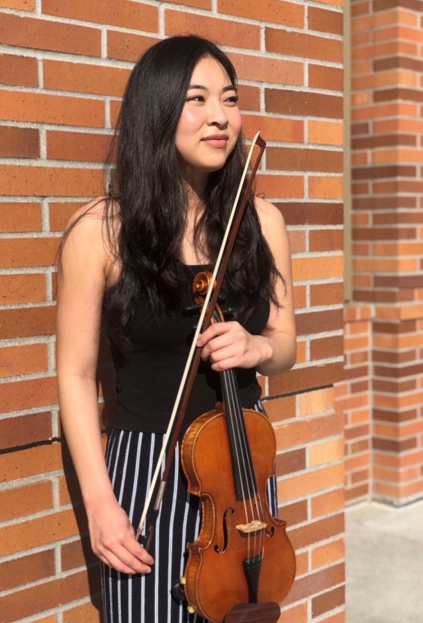 Smiling young woman with long dark hair wearing black and white striped pants and black tank top, holding a violin.